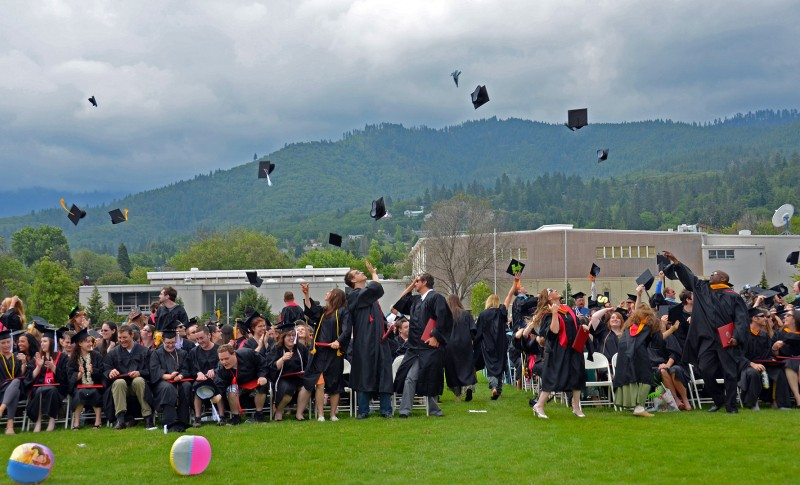 southern oregon university graduates throw their caps into the air in celebration