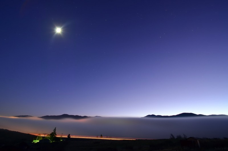 moon and stars look down over ashland engulfed in fog
