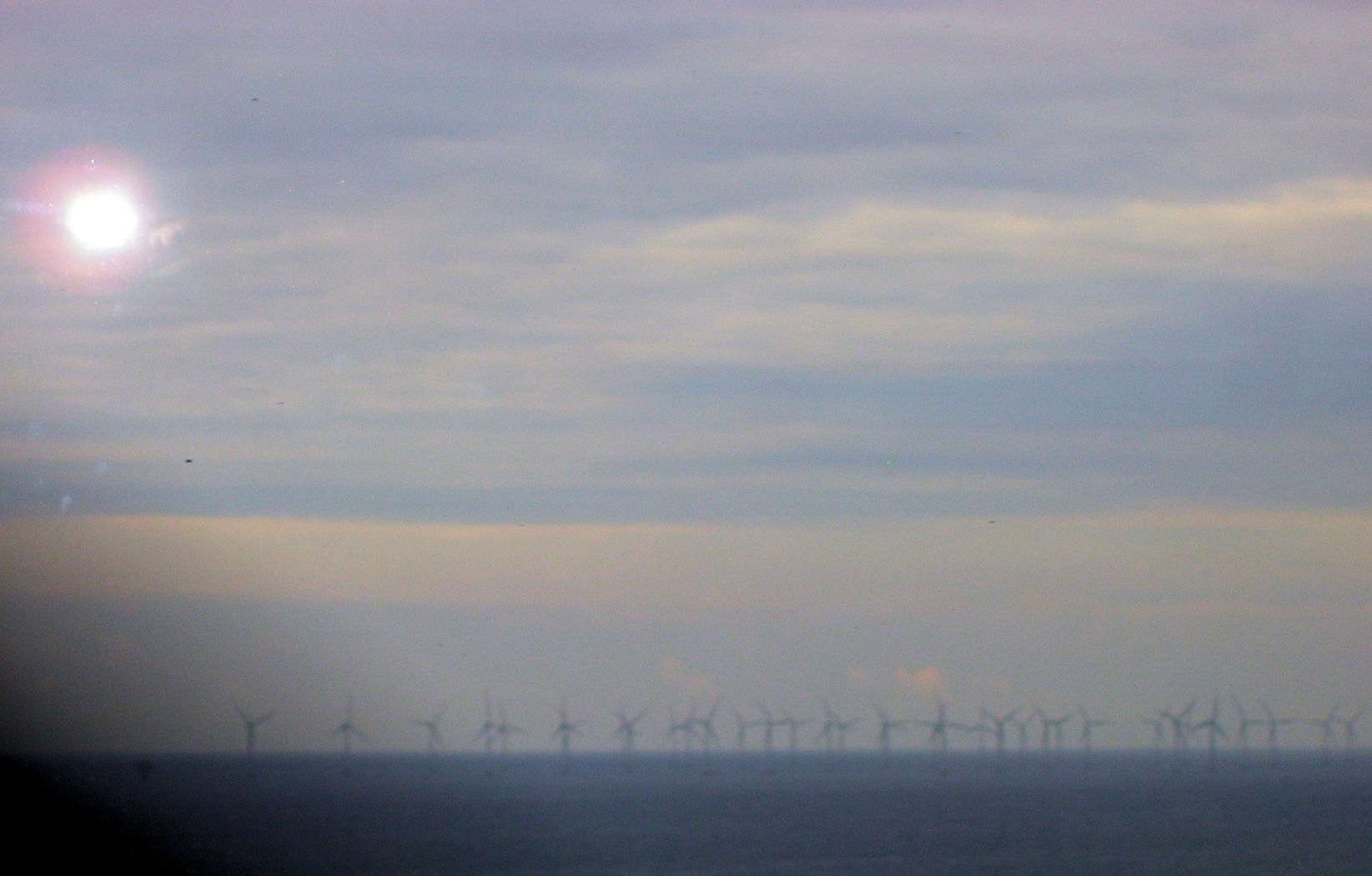 windmills at sunrise in the sea between denmark and sweden
