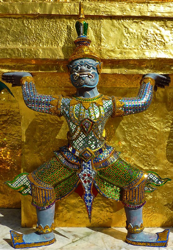 thai buddhist demon temple guardian holding up golden stupa