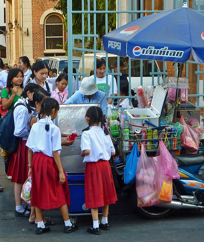 thai girls buying soda from street vendor