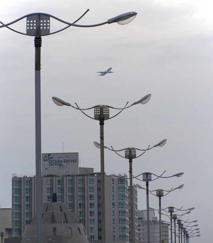 Jeju 제주 airplane flying over lampposts