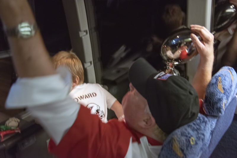 SOU football daytona coach howard and grandson and trophy and hand in the air